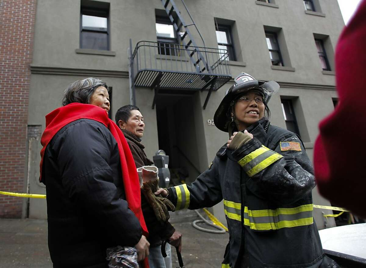 Lt. Anne Tam helps a couple of the tenants recovery some of their belongings from inside the burned building, after an early morning fire forced about 45 people from their apartment complex at 920 Montgomery Street, Calif. on Saturday Jan. 1, 2011