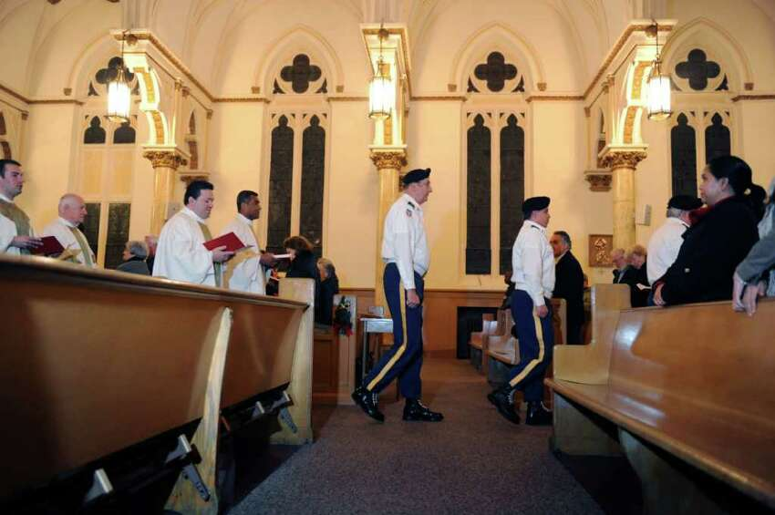 Members of the Stratford VFW Post 9460 color guard proceed out of St. Patrick's Church in Bridgeport, Conn. following mass Wednesday, Dec. 7, 2011.