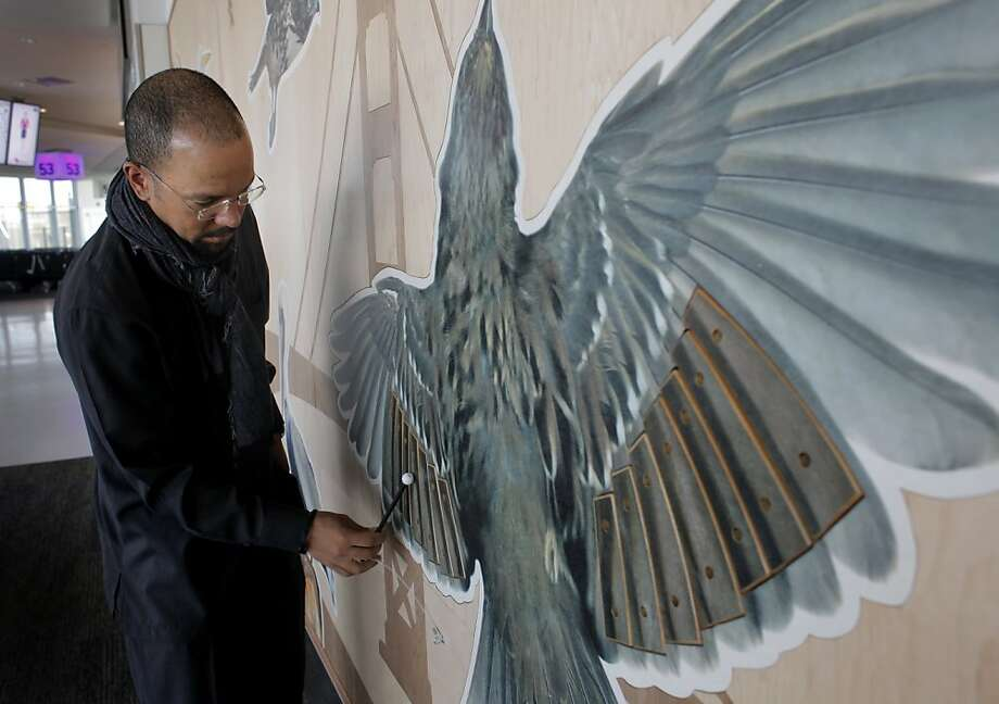 Artist Walter Kitundu stands in front of his artwork that is on display at the San Francisco International Airports Terminal 2, Wednesday April 6, 2011, in San Francisco, Calif. Photo: Lacy Atkins, The Chronicle