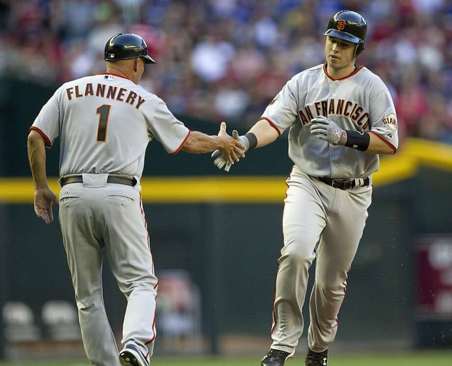 San Francisco Giants' Buster Posey is congratulated by Giants third base coach Tim Flannery (1) after  hitting a two-run home run against the Arizona Diamondbacks during the second inning of a baseball game on Saturday, April 16, 2011, in Phoenix. Photo: Matt York, AP