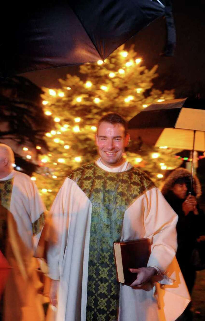 Fr. Peter Lenox stands in front of the glowing Christmas tree at St. Patrick's Church in Bridgeport, Conn. during the annual tree lighting to commemorate the 70th anniversary of the attacks on Pearl Harbor Wednesday, Dec. 7, 2011.