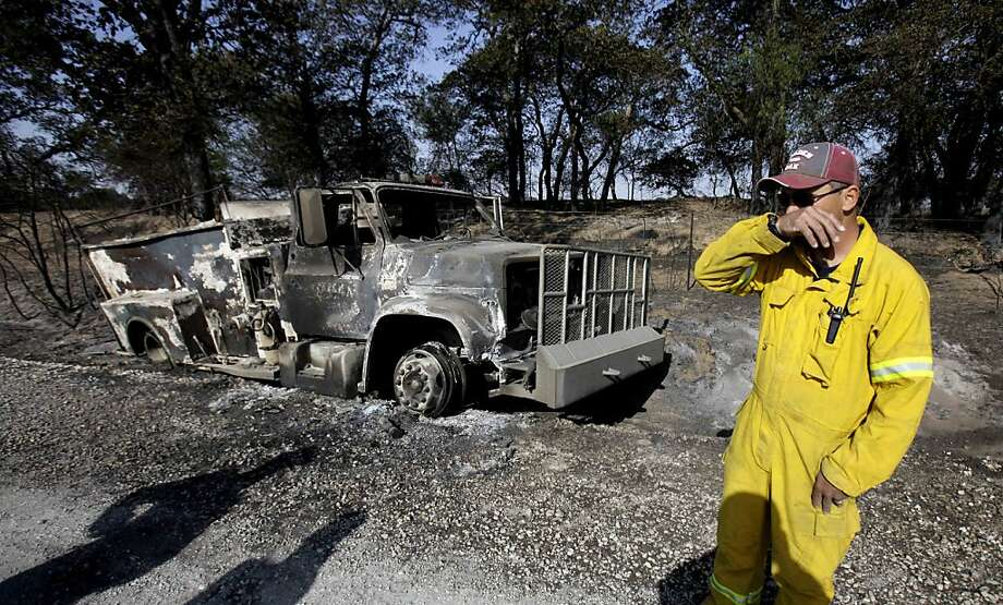 """Standing in front of a burned out fire truck, volunteer firefighter Steve Forbus pauses while he talks about the firefighter that was killed while trying to escape a wildfire that burned the truck in Eastland County near Gorman, Texas, Saturday, April 16,2011. """"It was a very emotional day for us,"""" said Forbus. Volunteer firefighter Gregory M. Simmons, 51, died as he and other firefighters fled the truck as it was being overrun by flames. Simmons fell in a ditch where the fire caught him, according to anofficial. Photo: LM Otero, AP"""