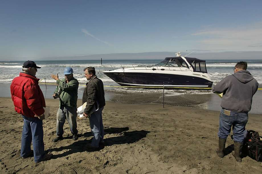 Workers discussing how to remove a stolen boat along Ocean Beach at Fulton Street. A drunken man celebrating his 35th birthday was arrested early Friday April 15, 2011, after he was found aboard a stolen boat that washed ashore on Ocean Beach in San Francisco. Photo: Michael Macor, The Chronicle