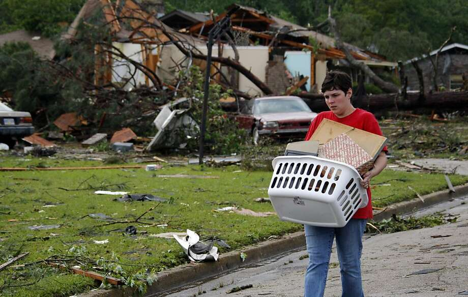 Rebecca Parks carries out salvaged personal items from the remains of a tornado damaged neighbor in east Clinton, Miss., Friday, April 15, 2011. Although her own home sustained damage, Parks and her children assisted neighbors in their cleanup. The statewas hit by a line of severe storms that spawned at least one tornado causing extensive damage and multiple injuries. Photo: Rogelio V. Solis, AP