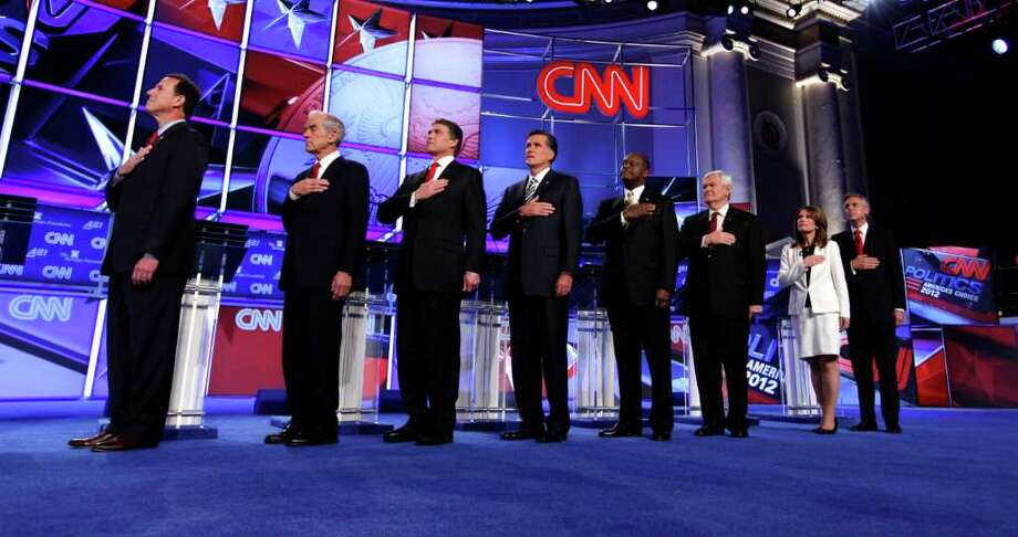 Republican presidential candidates from left, former Pennsylvania Sen. Rick Santorum, Rep. Ron Paul, R-Texas, Texas Gov. Rick Perry, former Massachusetts Gov. Mitt Romney, businessman Herman Cain, former House Speaker Newt Gingrich, Rep. Michele Bachmann, R-Minn., and former Utah Gov. Jon Huntsman stand for the National Anthem before a Republican presidential debate in Washington, Tuesday, Nov. 22, 2011. (AP Photo/Evan Vucci) Photo: Evan Vucci / Copyright 2011 The Associated Press. All rights reserved. This m
