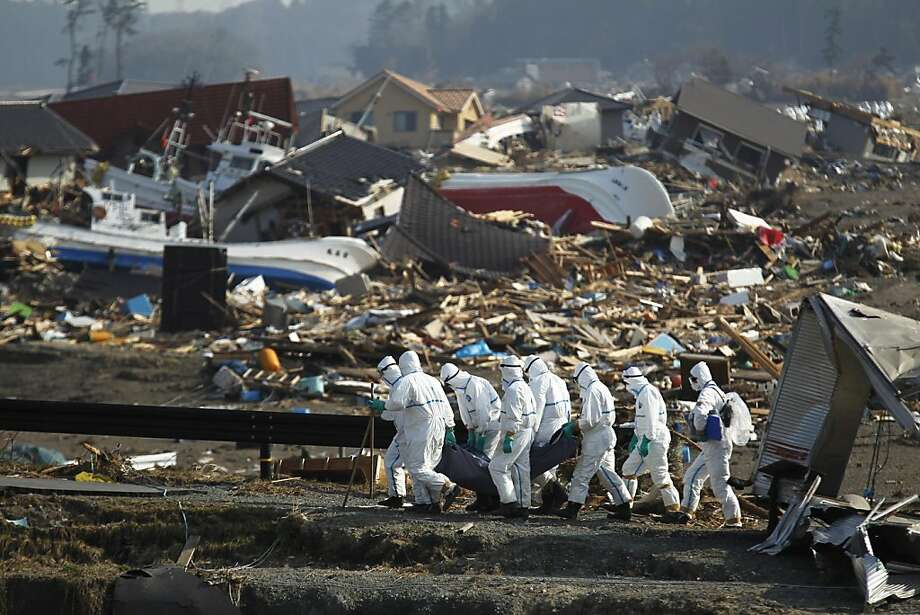 Japanese police officers carry a body during a search and recovery operation for missing victims in the area devastated by the March 11 earthquake and tsunami in Namie, Fukushima Prefecture, northeastern Japan, Friday, April 15, 2011. Photo: Hiro Komae, AP