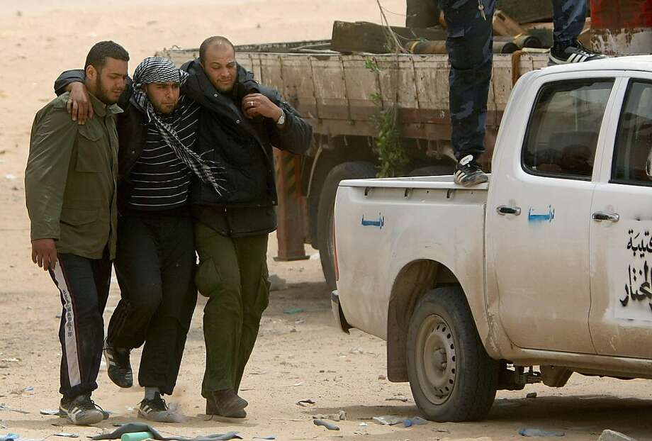 Libyan rebels help one of their injured comrade after Libyan regime forces pounded rebels with heavy artillery in the eastern town of Ajdabiya, on April 17, 2011. The intense bombardment of Ajdabiya came a day after at least eight people were killed and 27 wounded as the forces loyal to Libyan strongman Moamer Kadhafi fired rockets at rebel positions, hospital officials said. Photo: Marwan Naamani, AFP/Getty Images