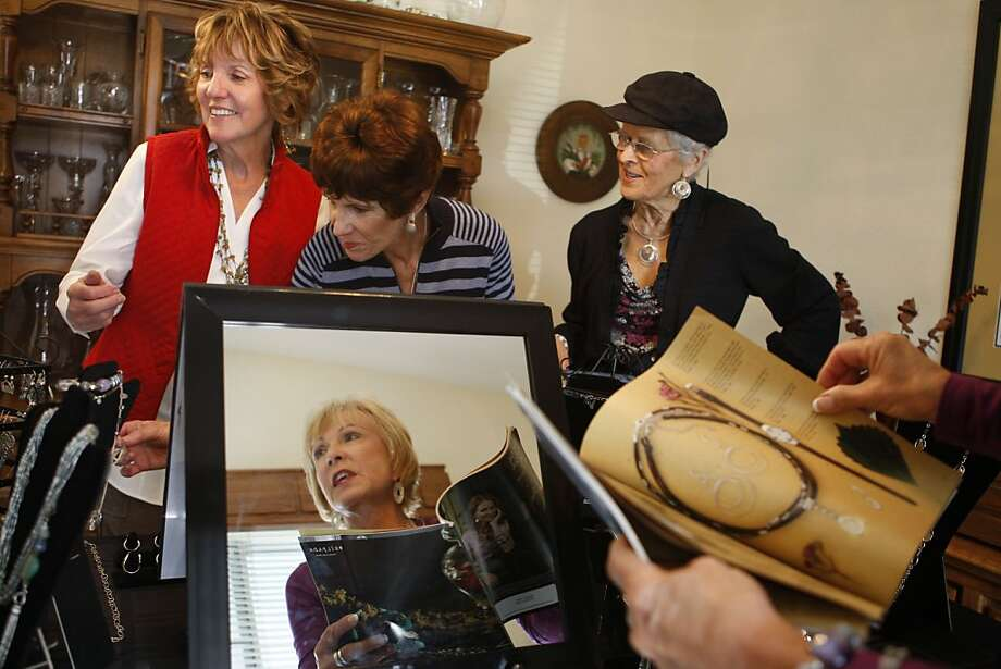Silpado customers Barbara Wobser, Pat Green and Astra Gabriel (left to right) look at pieces in the Silpado collection as sales srepresentative Sandy DeRodeff (bottom) looks for an item in the catalogue during a Silpado party held in Livermore Calif, on Thursday, April 14, 2011. Photo: Alex Washburn, The Chronicle