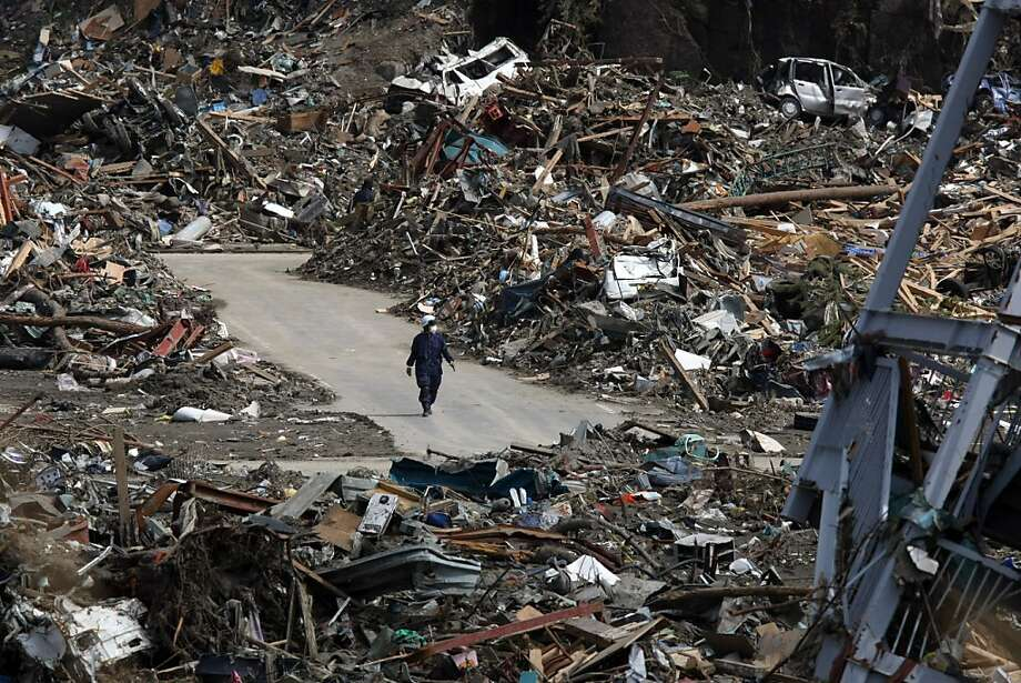 A man walks through tsunami debris stacked along a street in Rikuzentakata, Iwate prefecture, Japan, on Thursday, March 24, 2011. Japan 's government estimated the damage from this month's record earthquake and tsunami at as much as 25 trillion yen ($309 billion), an amount almost four times the hit imposed by Hurricane Katrina on the U.S. Photographer: Tomohiro Ohsumi/Bloomberg Photo: Tomohiro Ohsumi, Bloomberg