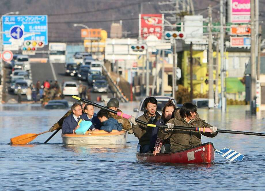 People evacuate with small boats down a road flooded by the tsunami waves in the city of Ishinomaki in Miyagi prefecture on March 12, 2011 a day after an 8.9 magnitude quake and tsunami hit the region. An explosion and feared meltdown at a Japanese nuclear plant on March 12 exposed the scale of the disaster facing the country after the massive quake and tsunami left more than 1,000 dead. Photo: Jiji Press, AFP/Getty Images