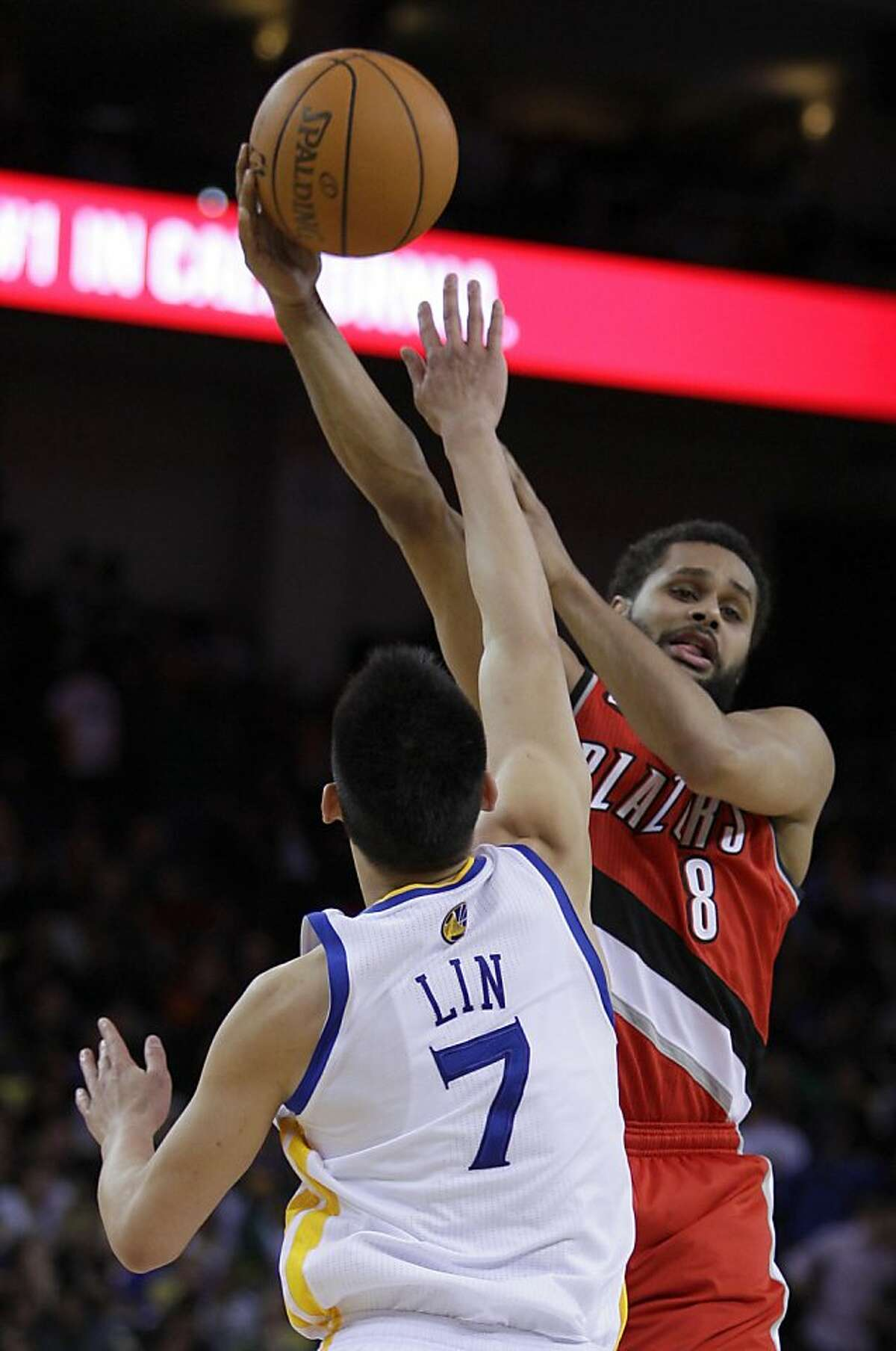 Portland Trail Blazers' Patrick Mills, right, passes away from Golden State Warriors' Jeremy Lin during the second half of an NBA basketball game Wednesday, April 13, 2011, in Oakland, Calif.