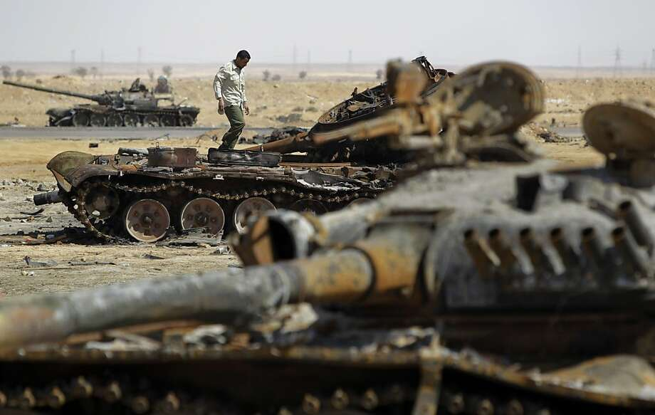 A rebel fighter stands on previously-destroyed pro-Gadhafi forces tanks, on the outskirts of Ajdabiya, Libya, Tuesday, April 12, 2011. Moammar Gadhafi's forces fired rockets along the eastern front line and shelled the besieged city of Misrata on Tuesdayas France said NATO should be doing more to take out the regime's heavy weaponry targeting civilians. Photo: Ben Curtis, AP