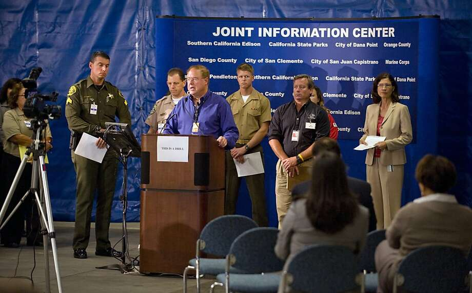 Surrounded by local and state agency officials, Gil Alexander spokesman for Southern California Edison, speaks  during a mock news conference at a makeshift emergency center at Edison's Saddleback Service Center, in Irvine, Calif. on Tuesday, April 12, 2011.   A month after Japan's devastating earthquake and tsunami, government officials participated Tuesday in a drill involving a fake disaster scenario at California's San Onofre Nuclear Generating Station.   While the drill was not prompted by events unfolding in Japan, officials say lessons from the disaster overseas could come up in discussions on how to handle the mock scenario. Photo: Mark Rightmire, AP