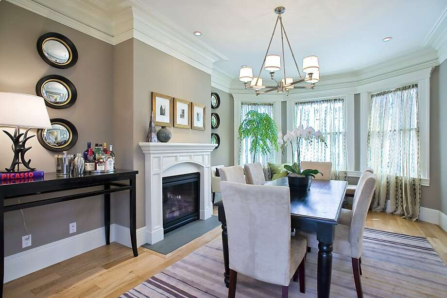 The foyer opens up to the formal dining room, which has crown molding and a gas fireplace. Photo: OpenHomesPhotography.com
