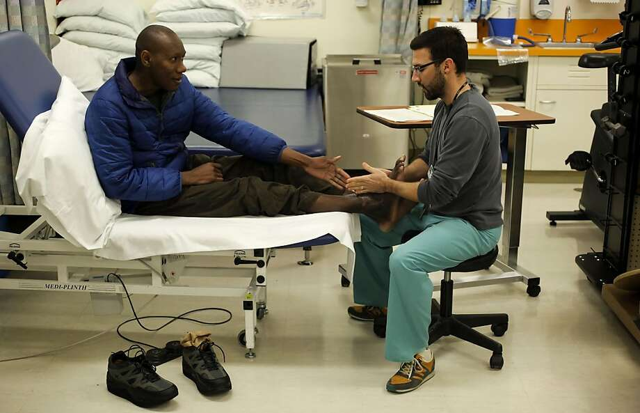 Jean Xavier, (left) works with his physical therapist, Joe Caballero, at San Francisco General Hospital on Friday Mar. 25, 2011, in San Francisco, Ca. Jean Xavier was badly injured in the Jan. 2010 Haitian earthquake, after six weeks in Haiti he came to San Francisco for care, where doctors were able to save his crushed leg from amputation, after six surgeries and a year later he is walking again. Photo: Michael Macor, The Chronicle