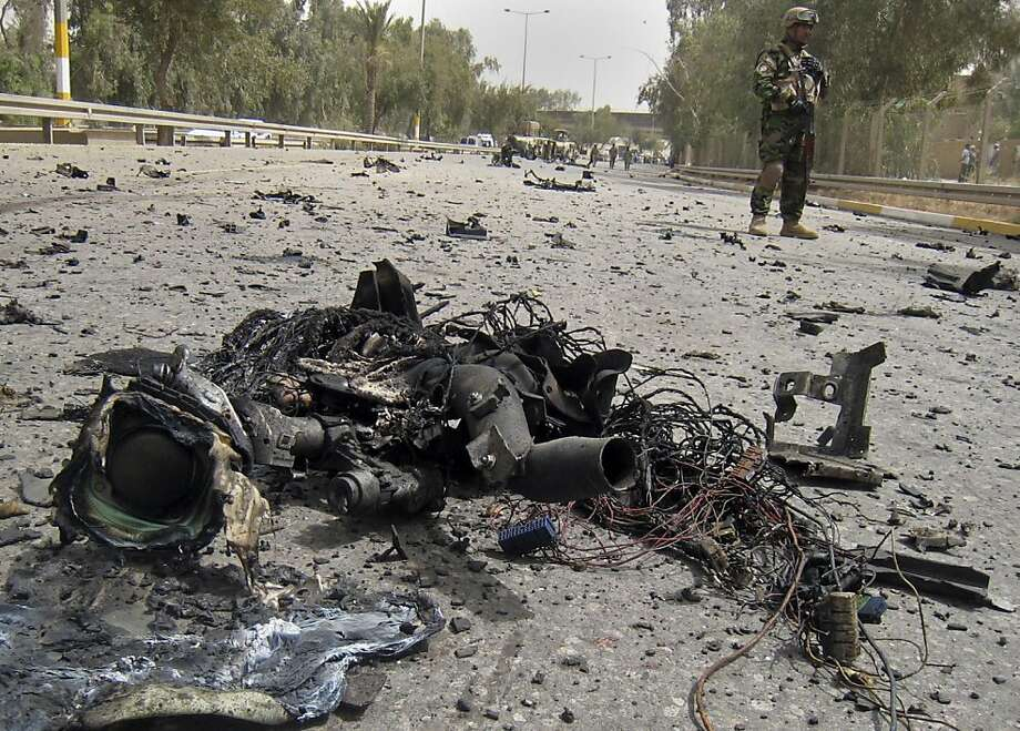 An Iraqi soldier secures the scene of a suicide car bomb in Baghdad, Iraq, Monday, April 18, 2011. Suicide bombers detonated two explosives-packed cars Monday outside Baghdad's heavily fortified Green Zone, killing and wounding several of people, police said. (AP Photo) Photo: AP