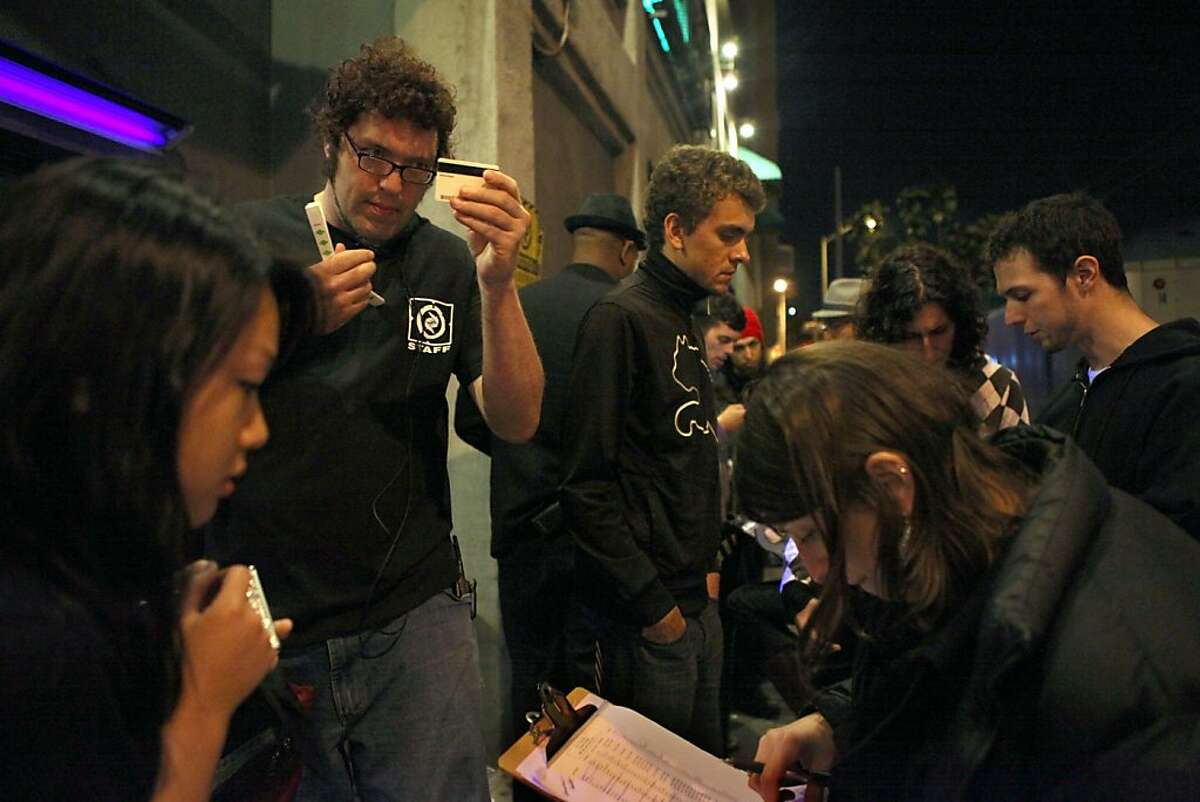 Security staff David Pomije (left) checking identification outside of the entrance of DNA Lounge in San Francisco, Calif., as names are checked on the guest list on Friday, April 15, 2011.