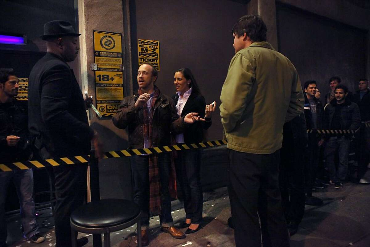 Security staff Sam Craig (left) checking identification of Noah Raizman and Courtney Cutter from Washington outside of the entrance of DNA Lounge in San Francisco, Calif., on Friday, April 15, 2011.