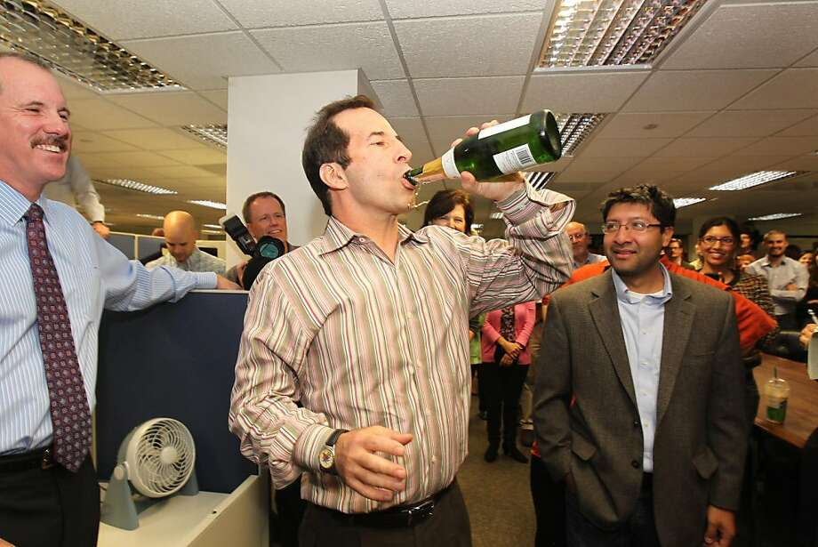 Los Angeles Times reporter Jeff Gottlieb lifts a bottle of champagne after winning the 2011 Pulitzer Prize for Public Service Monday, April 18, 2011. Gottlieb and fellow reporter Ruben Vives, right, won the award for their  exposure of corruption in the small California city of Bell where officials tapped the treasury to pay themselves exorbitant salaries, resulting in arrests and reforms. On the left is Los Angeles Times editor Russ Stanton. Photo: Christina House, AP