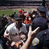 Brian Wilson runs the championship flag through the crowded bleachers before the start of the Giants' Opening Day game at AT&T Park against the St. Louis Cardinals on Friday.