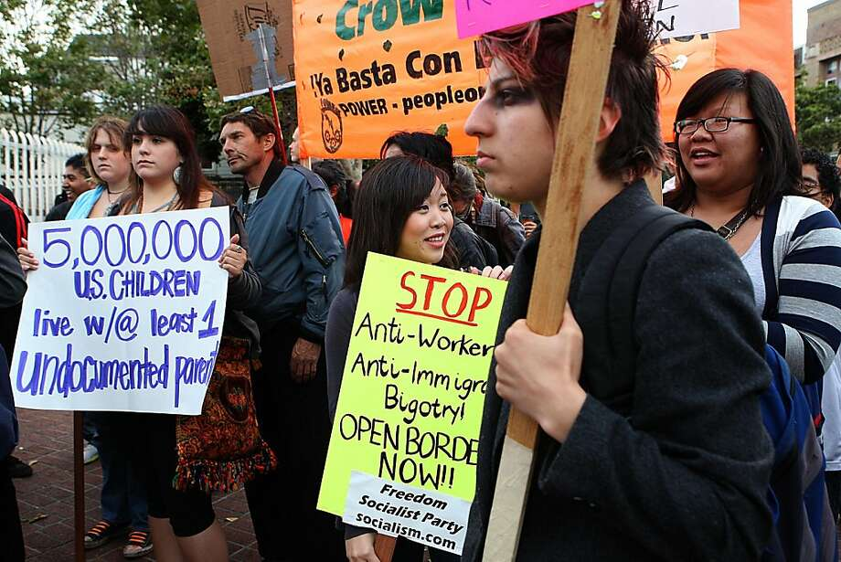 Shane Oanes (front, right), 24 years old, from San Francisco, and Josephine Saechao (yellow sign), 17 years old, from Richmond attend a rally on Mission at 24th streets in reaction to the Arizona immigration law which went into effect today in San Francisco, Calif., on Thursday, July 29, 2010. Photo: Liz Hafalia, The Chronicle