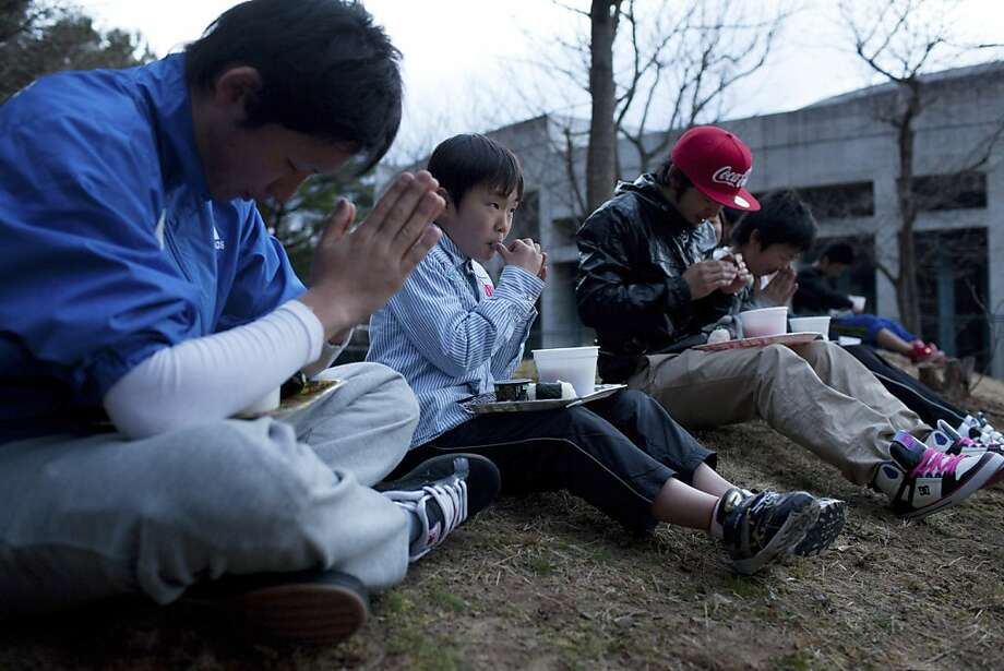 Kei Endo (C), 10, eats relief food with other youths outside an evacuation centre suffering from power cuts following aftershocks in Shichigahama town, Miyagi prefecture on April 8, 2011. A powerful aftershock rocked Japan's tsunami zone, killing at leasttwo and triggering new concerns over nuclear power plants in a region still grappling with an atomic emergency. Photo: Yasuyoshi Chiba, AFP/Getty Images