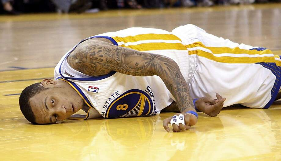 Golden State Warriors guard Monta Ellis lies on the court after being fouled by Sacramento Kings power forward DeMarcus Cousins in the fourth quarter of an NBA basketball game in Oakland, Calif., Sunday, April 10, 2011. Ellis left the game and did not return. The Kings won 104-103. Photo: Jeff Chiu, AP