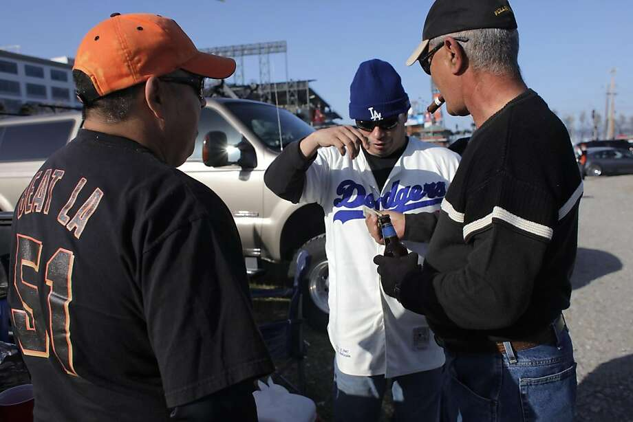 Chris Gallego, left and Frank Castillo, Dodger fan,  turn down money for a beer from Giants fan John Pecora in the parking lot outside the gates at AT&T Park opened for the first Giants and Dodgers game,  Monday April 11, 2011, in San Francisco, Calif. Photo: Lacy Atkins, The Chronicle