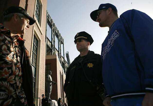 Tom Rouse from Sonoma (left) chats with police lieutenant Bill Roualdes (center) and Mauro Gonzalez (right), from Fresno. Despite rooting for different teams Rouse and Gonzalez are friends attending the game together. There is increased security at the Giants vs. Dodgers game in San Francisco on Monday, April 11, 2011. Photo: Anna Vignet, The Chronicle