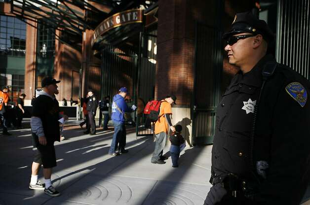 SFPD officer Scott Cairel stands outside the doors to AT&T park while fans enter the stadium. There is increased security at the Giants vs. Dodgers game in San Francisco on Monday, April 11, 2011. Photo: Anna Vignet, The Chronicle