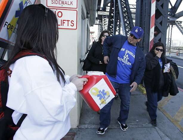 Paul Alfaro, center, a Los Angeles Dodgers fan from San Jose, Calif., reaches for his wallet to make a donation for Bryan Stow, the paramedic who was beaten at Dodger Stadium earlier this month, before the San Francisco Giants' baseball game against the Dodgers in San Francisco, Monday, April, 11, 2011. Collecting the donation at left is Whitney Hall, an emergency medical technician with Sacramento County. The Giants beefed up security for a three-game series against the Dodgers. Photo: Eric Risberg, AP