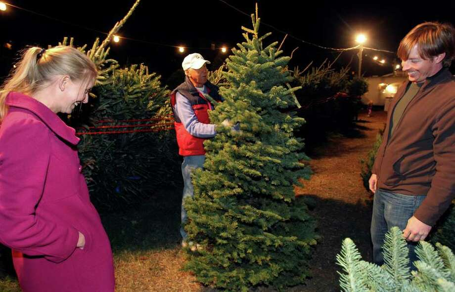Bob Hoppe (center) assists as Clay and Jessie Embrey select a Christmas tree at the Alamo Heights Optimist Tree lot. Retailers say sales are up. Photo: TOM REEL, SAN ANTONIO EXPRESS-NEWS / © 2011 San Antonio Express-News