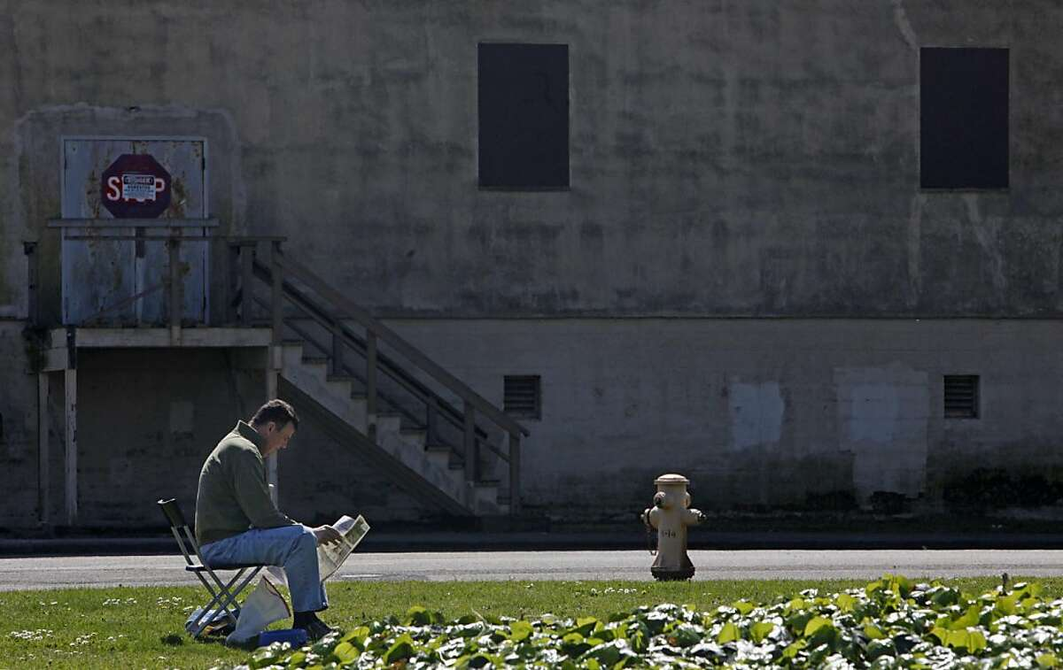 R. Scott of San Francisco reads a newspaper while sitting in the sun during an outing with his dog, Sam Sam, on Monday, March 28, 2011 in Treasure Island, San Francisco, Calif.R. Scott of San Francisco reads a newspaper while sitting in the sun during an outing with his dog, Sam Sam, on Monday, March 28, 2011 in Treasure Island, San Francisco, Calif.