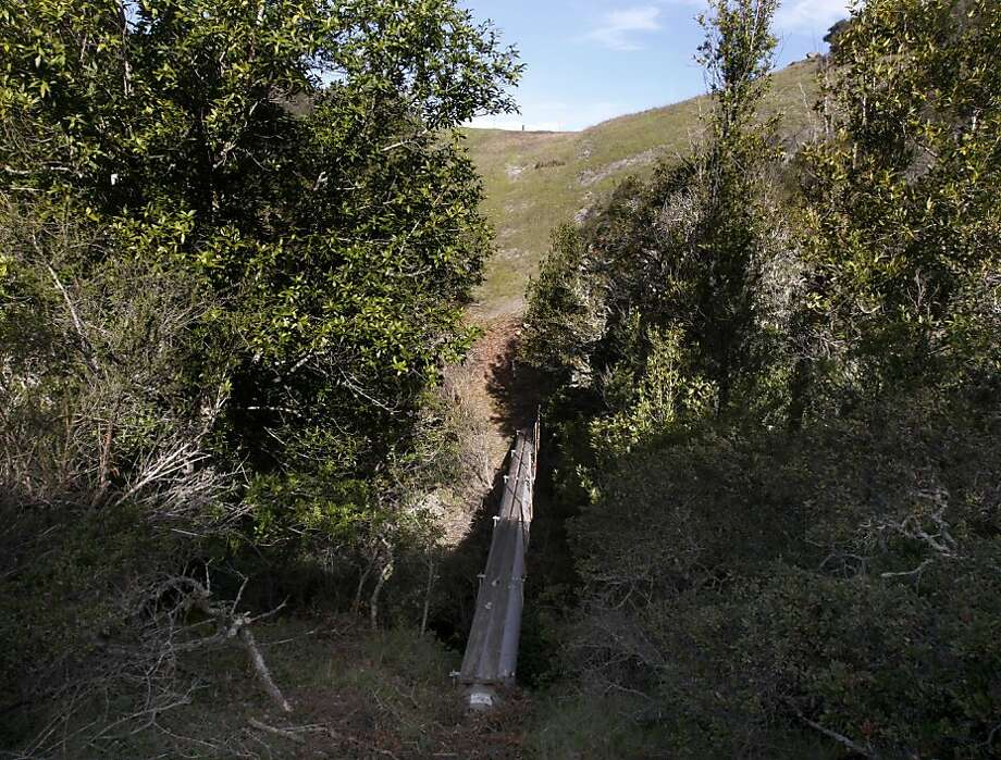 An exposed section of PG&E's Line 109 gas transmission pipeline spans a creek on a steep hillside in Redwood City, Calif. on Friday, April 1, 2011. Photo: Paul Chinn, The Chronicle