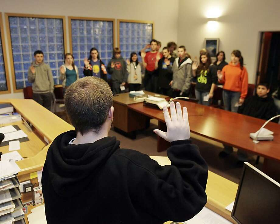 ED NOTE: Last names of juveniles have been off for privacy reasons.  Ron, the 17-year-old bailiff, swears in the jury of juvenile peers on Jose's case in San Rafael, Calif., on Tuesday, March 8, 2011. Marin teens who are first time offenders of small crimes (shoplifting, pot possession) are tried and sentenced by a jury of their peers in Marin Youth Court. Teens serve as prosecutors, defense attorneys and the bailiff. The program is an alternative sentencing program that gives young people a chance to wipe their record clean and start over. Photo: Carlos Avila Gonzalez, The Chronicle