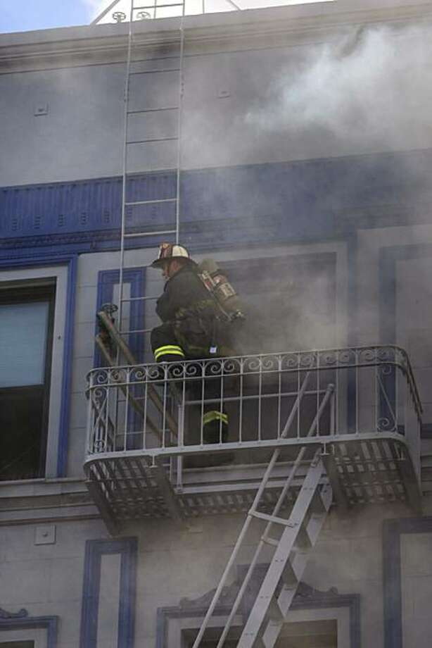 A San Francisco firefighter climbs on a fire escape as others work on a structure fire at 111 Taylor St. on Thursday. The building is a halfway house for parolees. Photo: Carlos Avila Gonzalez, The Chronicle