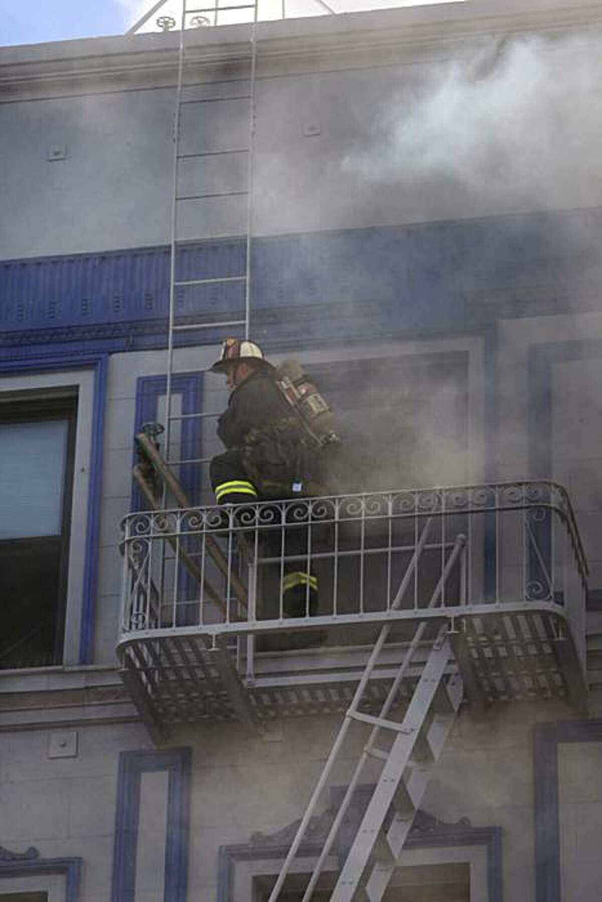 A San Francisco firefighter climbs on a fire escape as others work on a structure fire at 111 Taylor St. on Thursday. The building is a halfway house for parolees.