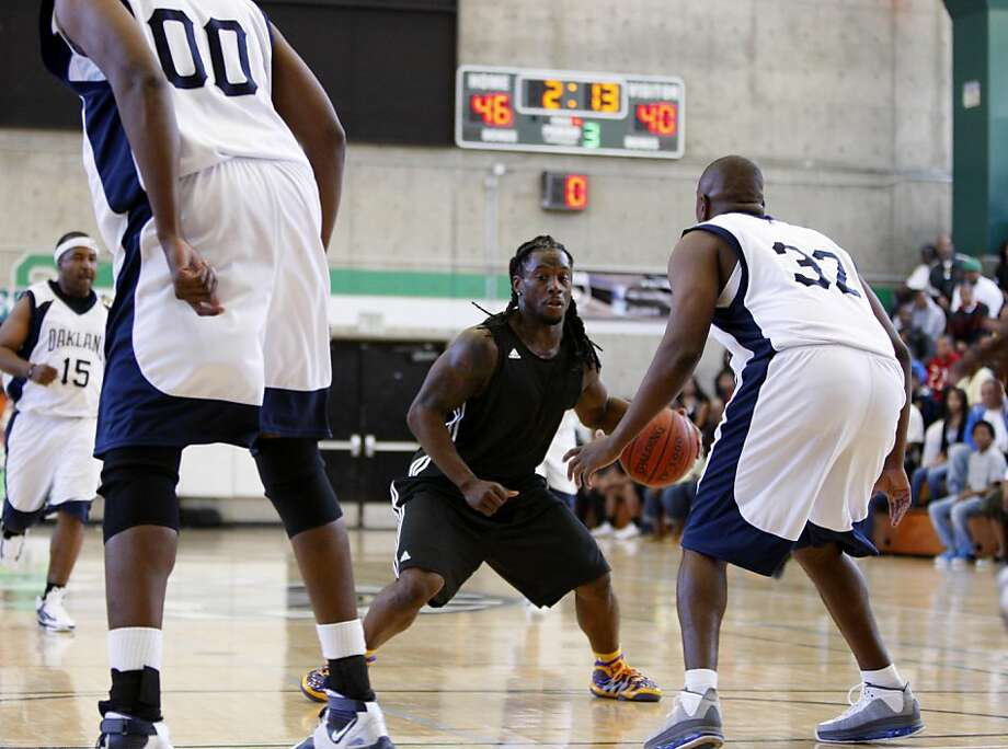 Davone Bess (center) tries to get through Gary Lewis (00) and Sean Washington (32) during a NFL players versus Oakland Police Officer's Association charity basketball tournament at Laney College in Oakland, Calif., on Saturday, April 9, 2011. The NFL players beat the OPD 69-68. Photo: Thomas Levinson, The Chronicle