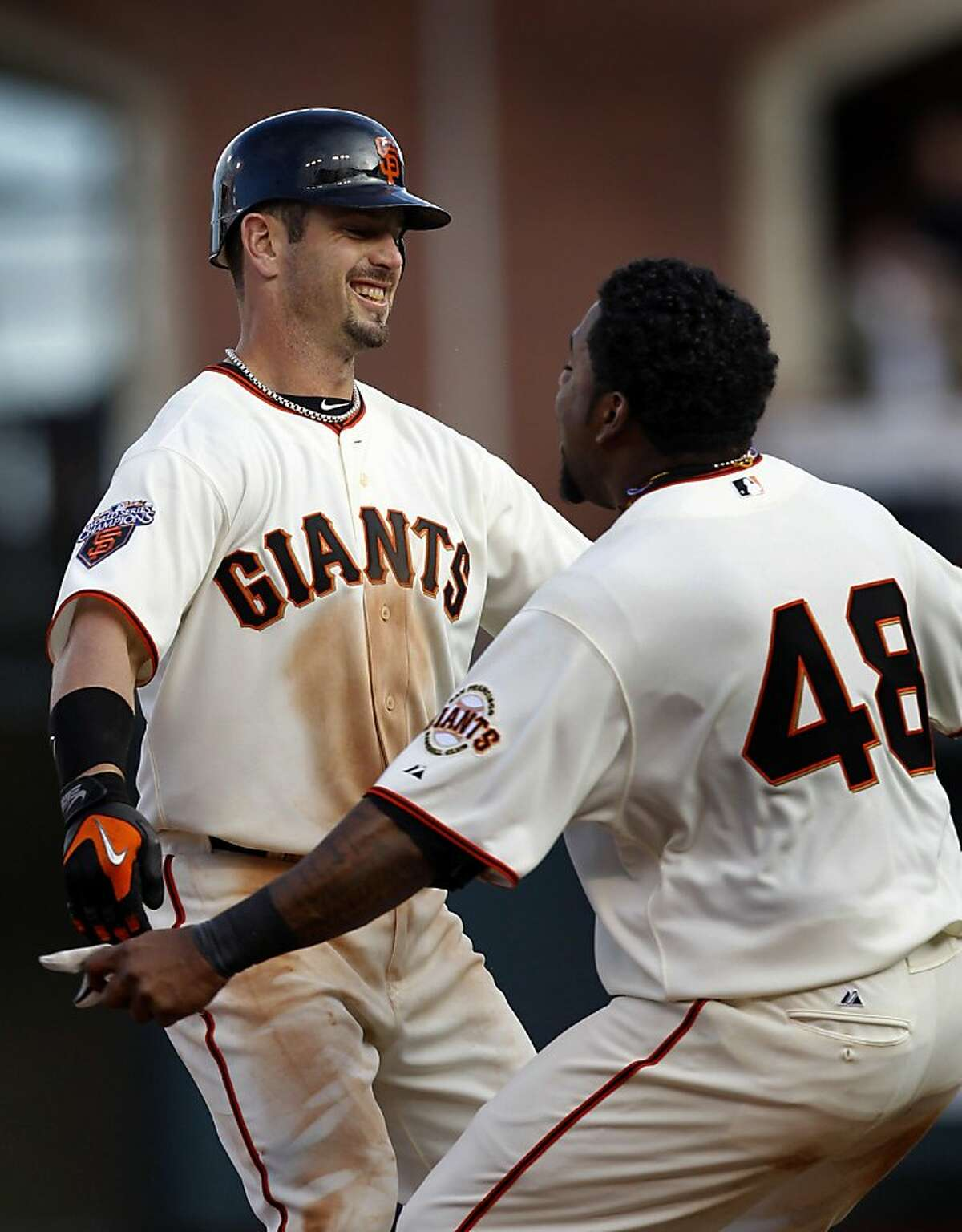 Pablo Sandoval is the first to greet Aaron Rowand after Rowand's game-winning RBI single in the 12th inning of the Giants' home opener against the St. Louis Cardinals at AT&T Park in San Francisco on Friday.