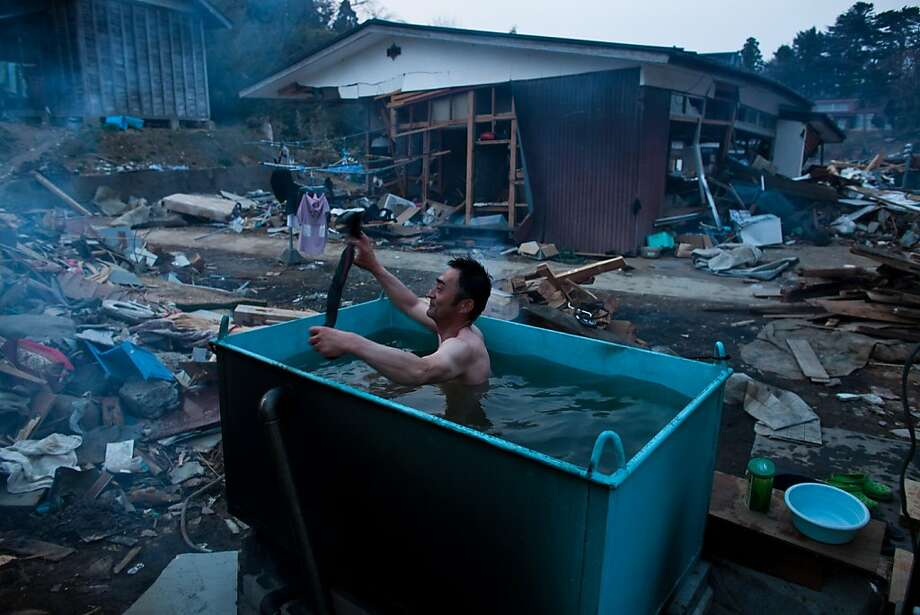 A resident takes an out door bath amongst tsunami devastation in Kesennuma city, Miyagi prefecture on April 14, 2011.  Japan's seismologists were so entrenched in outdated beliefs about seismic hazard that they became blinkered to the risk of the March 11mega-quake, a commentary in a top science journal charged. Photo: Yasuyoshi Chiba, AFP/Getty Images