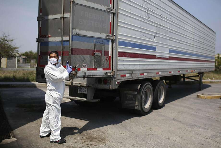 A morgue employee prepares to unload a body, found in a mass grave, from a refrigerated truck into the local morgue in Matamoros, northern Mexico, Friday April 8, 2011. Investigators have uncovered 13 more bodies in mass graves in the northern state of Tamaulipas, where 59 dead were exhumed earlier this week, officials said Friday. Photo: Alexandre Meneghini, AP