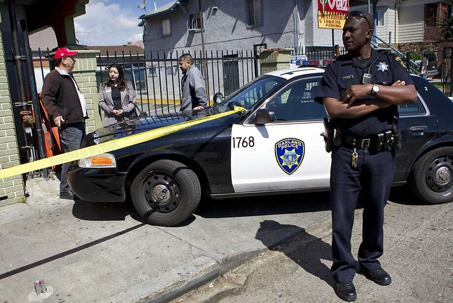 """Oakland police officer R. Ward keeps an eye on the area near where Jesus """"Chuy"""" Campos was shot while headed to work at his restaurant Otaez Mexicatessen in the Fruitvale District of Oakland, Calif., on Friday, April 8, 2011.  Campos was shot shortly after 5:30 a.m. Friday morning near a side door to the restaurant and later died of his injuries. Photo: Laura Morton, Special To The Chronicle"""