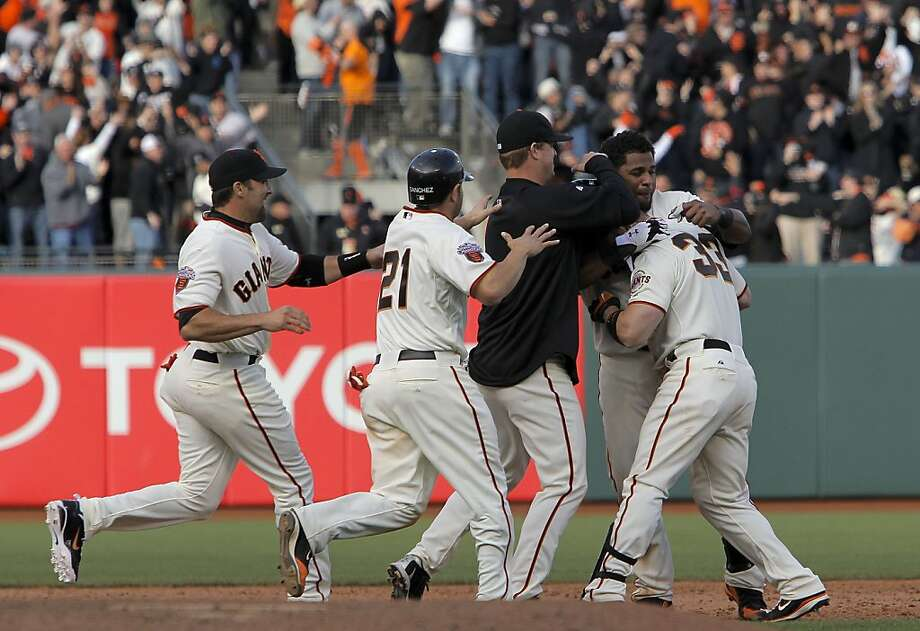 The Giants' Aaron Rowand (right) is swarmed by his teammates after his game winning hit in the bottom of the 12th inning as the San Francisco Giants win their home opener against the St. Louis Cardinals at AT&T Park in San Francisco on Friday. Photo: Michael Macor, The Chronicle