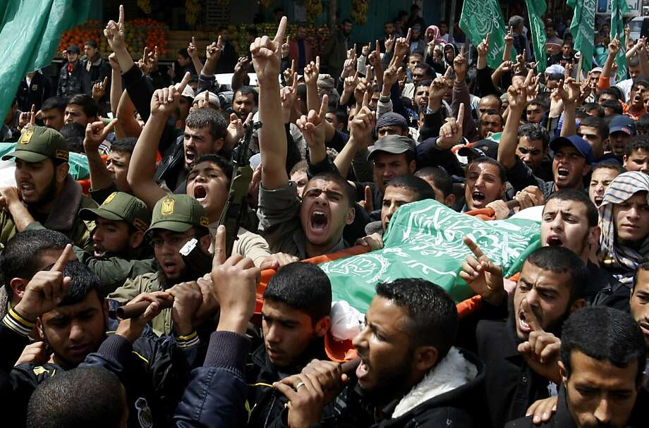 Palestinians carry the bodies of Hamas militants killed on Thursday's attack, during a funeral in Rafah, southern Gaza Strip, Friday, April 8, 2011. Israeli aircraft and ground forces struck Gaza on Friday in a surge of deadly fighting sparked by a Palestinian rocket attack on an Israeli school bus the day before. Just over two years after rocket fire from Gaza drew a devastating Israeli incursion in the territory, Israel and Gaza's Hamas rulers seemed poised on the brink of another round of intense violence. Photo: Hatem Moussa, AP