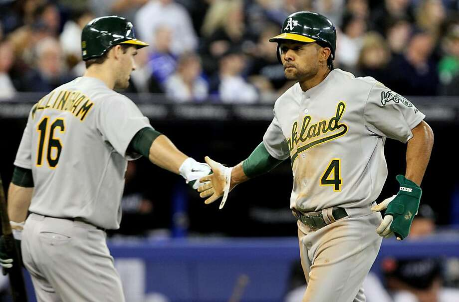 TORONTO, CANADA - APRIL 7: Coco Crisp #4 and Josh Willingham #16 of the Oakland Athletics celebrate run during MLB action between the Toronto Blue Jays and the Oakland Athletics at the Rogers Centre April 7, 2011 in Toronto, Ontario, Canada. Photo: Abelimages, Getty Images