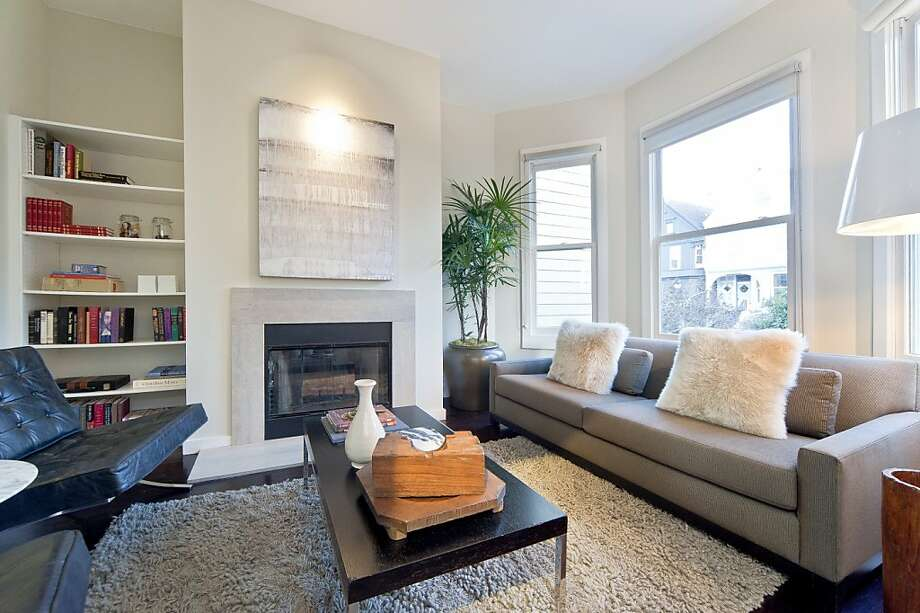 The living room has a wood-burning fireplace and features the hardwood flooring and recessed lighting found throughout the condo. Photo: OpenHomesPhotography.com