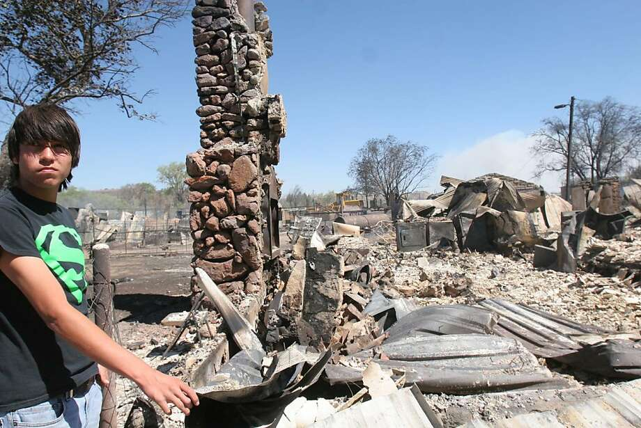 Isaiah Martinez stands in the rubble of his great-great-grandparents' home in Fort Davis, Texas on Monday, April 11, 2011.   Powerful winds that sent walls of flame through parched ranchland in and around the West Texas communities of Fort Davis and Midland, incinerating more than 60 homes during the weekend and killing livestock and horses, took pity by directing the fires to largely unpopulated open spaces north and east of the cities. Photo: Alberto Halpern, AP
