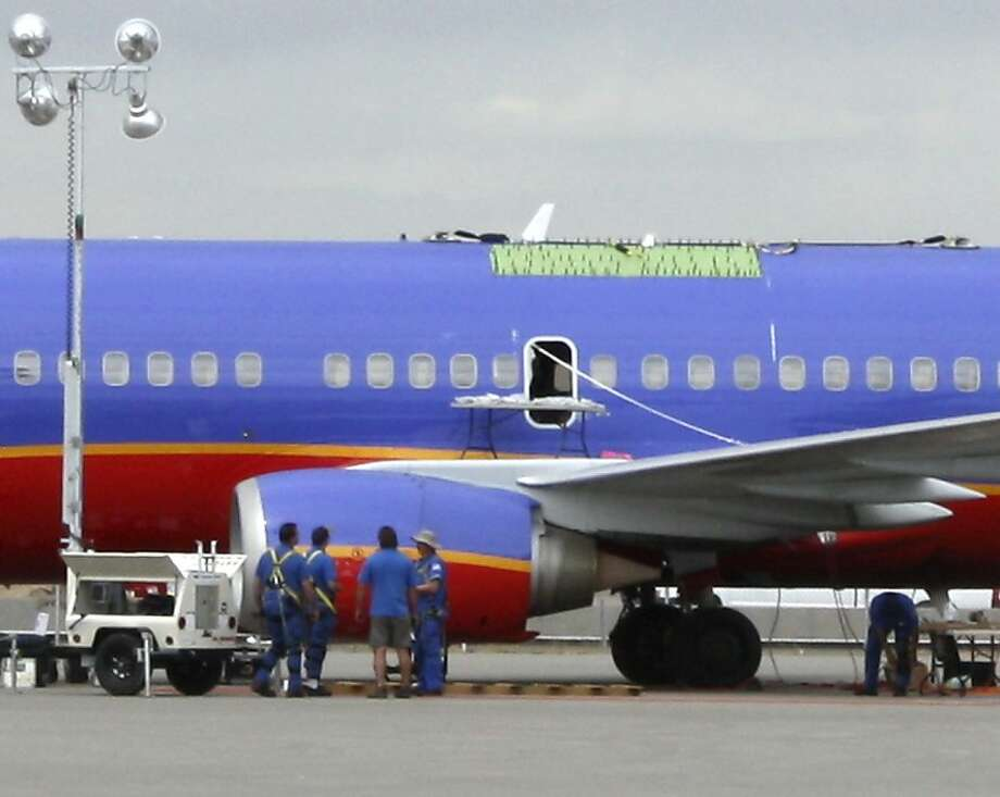 Southwest Airlines mechanics work near a Boeing 737 on a tarmac in Yuma, Ariz.,  on Wednesday, April 6, 2011, after patching a large hole in the jetliner that made an emergency landing in southwestern Arizona last week. The plane has been sitting on the tarmac at a military base in Yuma, Ariz., since Friday when a hole tore open in the top of the plane carrying 118 people, but the company won't say when or if it will be put back in service. Photo: Gen Grosse, AP
