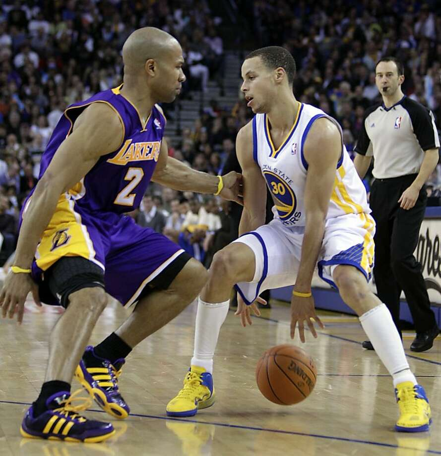Los Angeles Lakers' Derek Fisher, left, guards Golden State Warriors' Stephen Curry during the second half of an NBA basketball game Wednesday, April 6, 2011, in Oakland, Calif. Photo: Ben Margot, AP