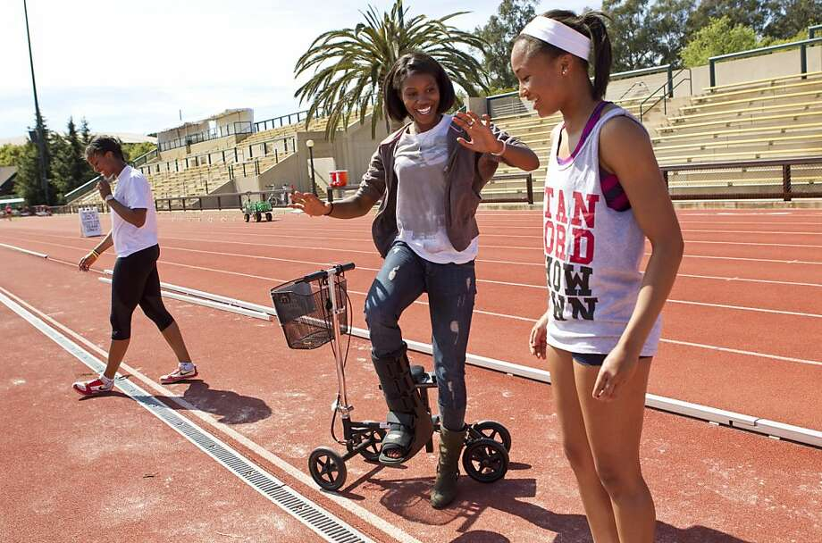 Erica McClain (center) helps Taylor Dewberry, a freshman Stanford track and field team member, with her technique while volunteer coaching during a practice at Stanford University in Palo Alto, Calif., on Wednesday, March 30, 2011.  McClain, an Olympic level triple jumper, recently suffered a compound fracture in two leg bones during a training accident, but is working to recover and still hopes to make the 2012 Olympic team. Photo: Laura Morton, Special To The Chronicle